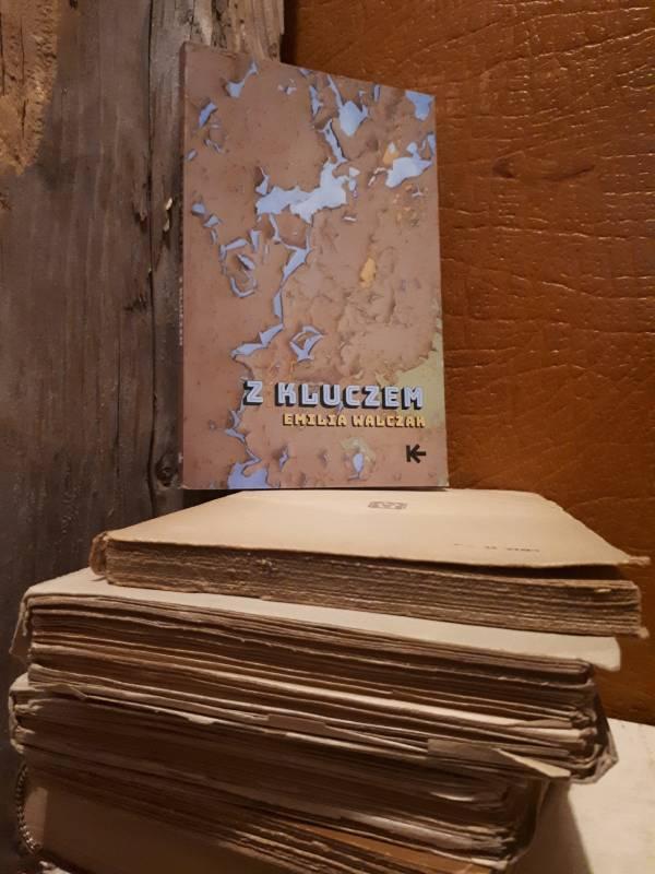 Podłoga była zasłana rozsypującymi się stosami książek, w kilku miejscach wciąż wznoszącymi się buńczucznie jak wieża Babel (cytat z powieści).